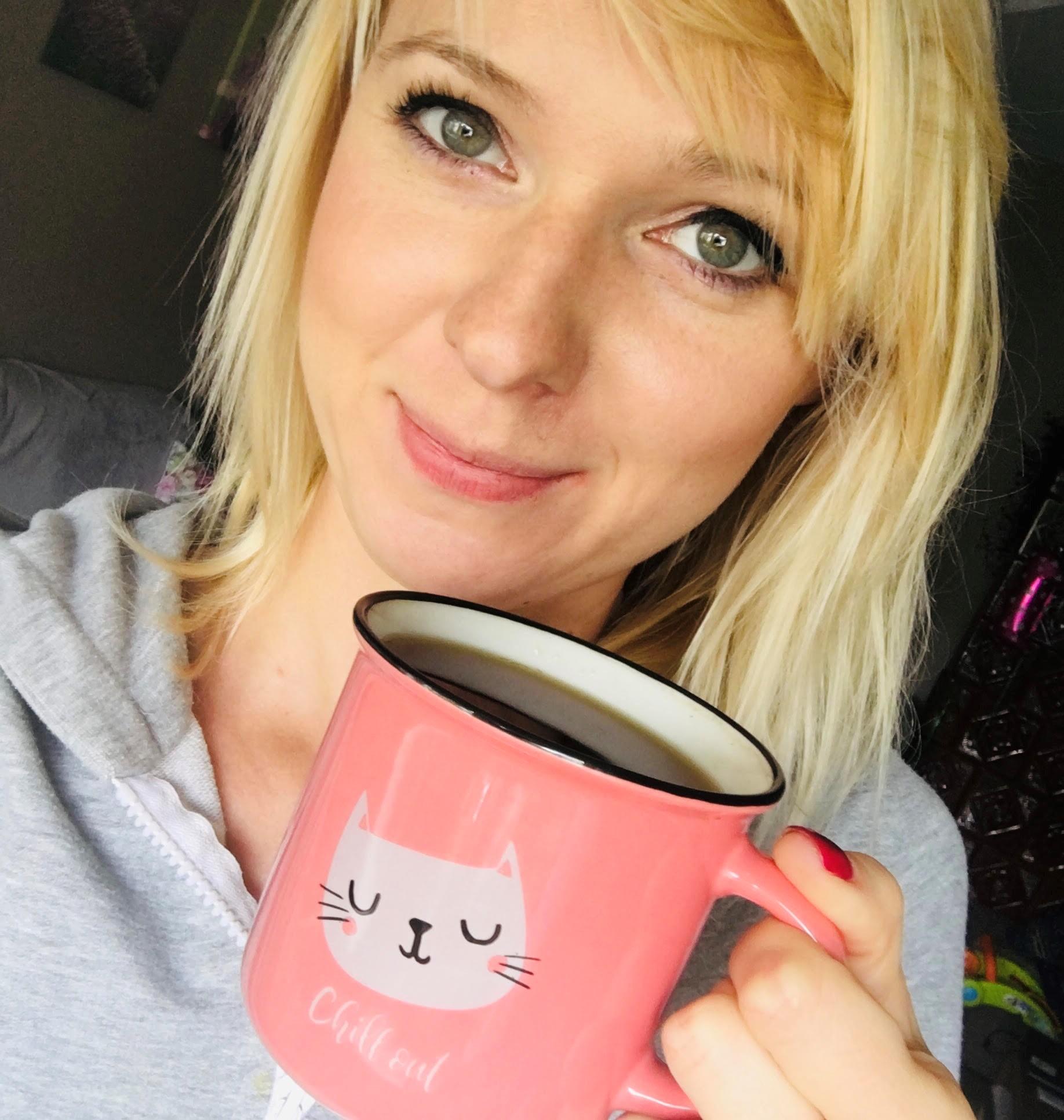 blondynka z różowym kubkiem z kotem z zielonymi oczami